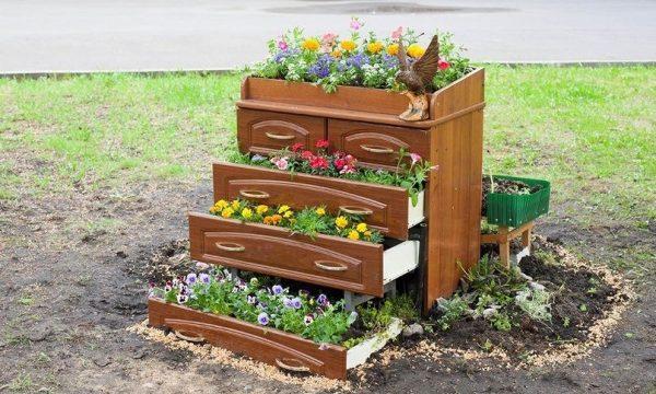 Клумба с цветами из мебели